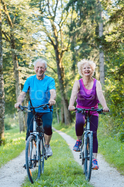 Happy and active senior couple riding bicycles outdoors Stock photo © Kzenon