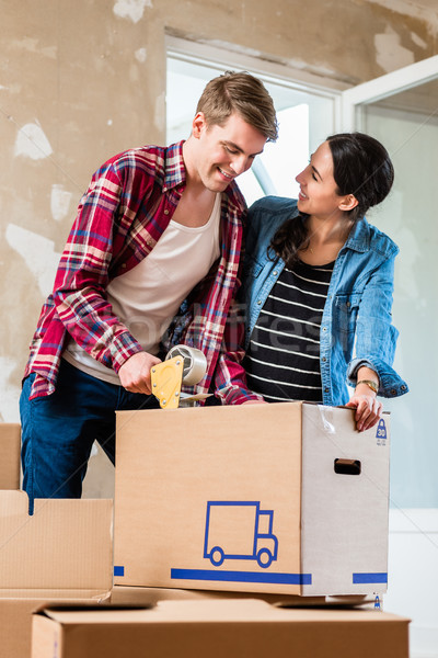 Young man and his girlfriend sealing a box while renovating their home Stock photo © Kzenon