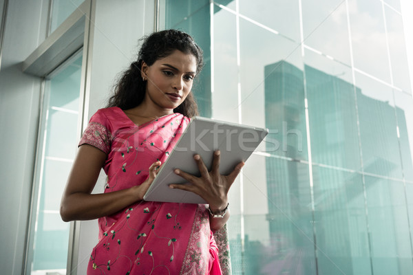 Portrait of young Indian woman using a tablet PC outdoors Stock photo © Kzenon