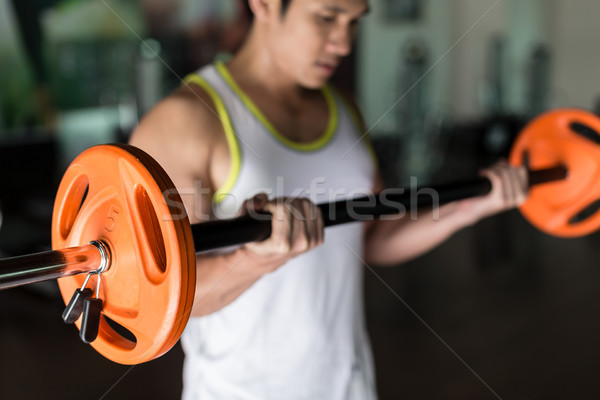 Vastbesloten jonge man barbell greep Stockfoto © Kzenon