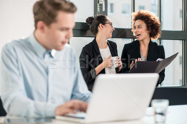 Two young cheerful female employees talking in the office Stock photo © Kzenon