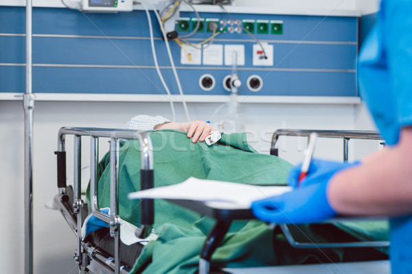 Nurse writing down data on patient in recovery room of modern hospital Stock photo © Kzenon