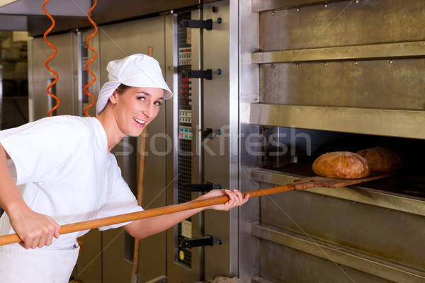 Female baker baking bread Stock photo © Kzenon