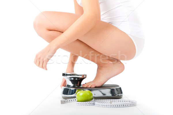 Young woman sitting on her haunches on a scale Stock photo © Kzenon