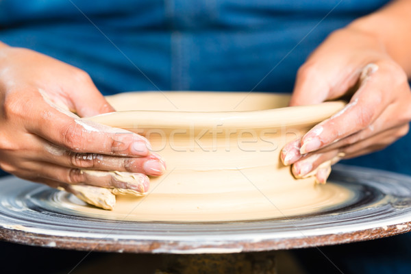 Potter creating clay bowl on turning wheel Stock photo © Kzenon