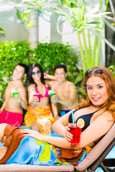 Asian friends partying at pool party in hotel Stock photo © Kzenon