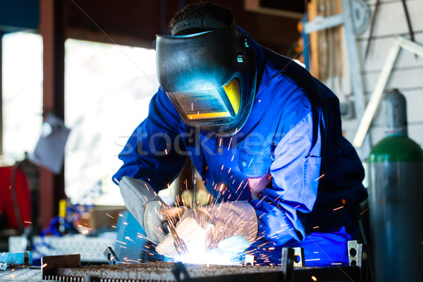 Welder welding metal in workshop with sparks Stock photo © Kzenon
