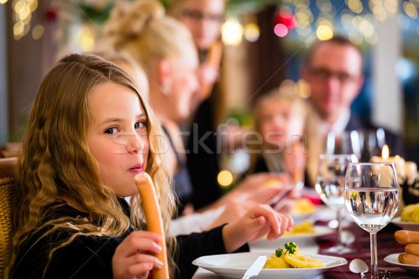 Family eating Christmas sausages for dinner Stock photo © Kzenon