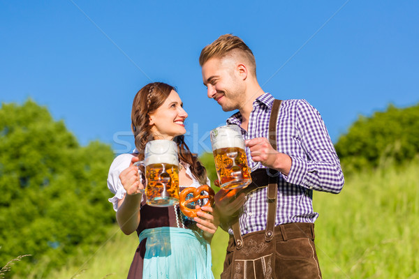 German couple in Tracht with beer and pretzel Stock photo © Kzenon