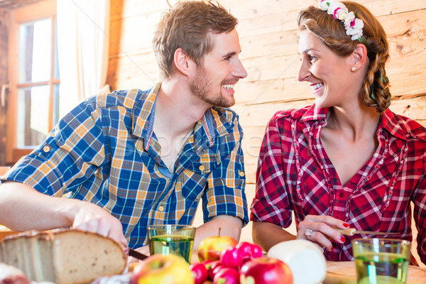 Man and woman eating food in mountain cabin Stock photo © Kzenon