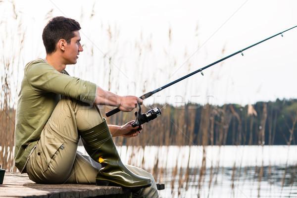 Man relaxing fishing or angling at lake Stock photo © Kzenon