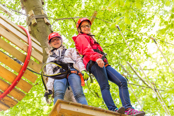 Sisters climbing in high rope course together Stock photo © Kzenon