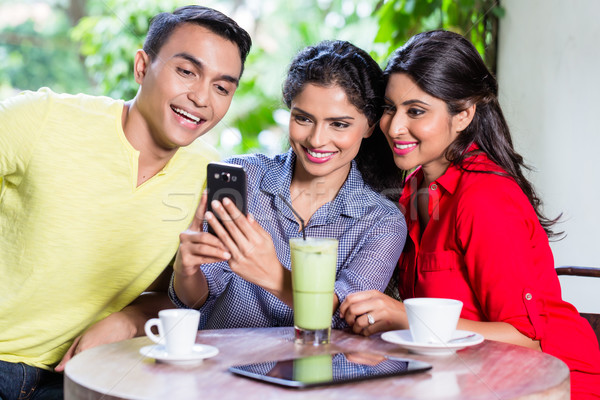 Indian girl showing pictures on phone to friends Stock photo © Kzenon