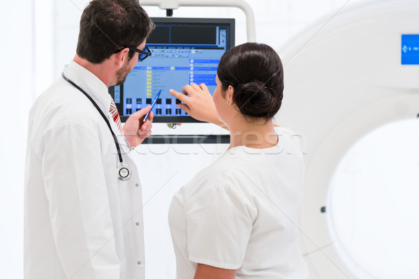 Doctor and nurse analyzing data of CT scan Stock photo © Kzenon