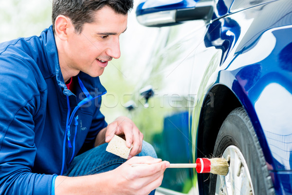 Man cleaning the alloy hubs on his car tyres Stock photo © Kzenon