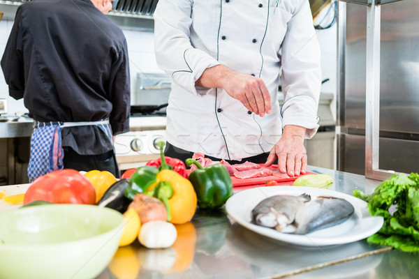 Chef putting salt on fish while cooking in kitchen Stock photo © Kzenon