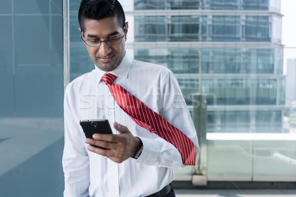 Businessman smiling while reading information on the mobile phon Stock photo © Kzenon