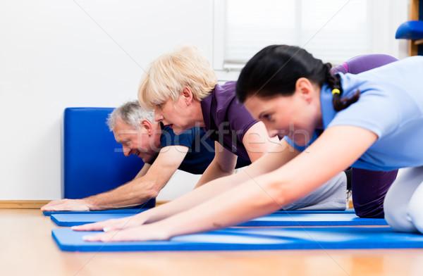Physio doing kinesitherapy with senior patients  Stock photo © Kzenon