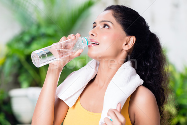 Portrait of healthy young woman drinking water during workout Stock photo © Kzenon