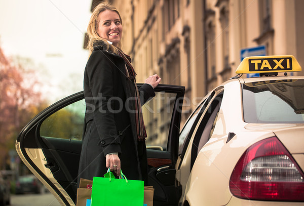 Young woman gets out of taxi carrying shopping bags Stock photo © Kzenon