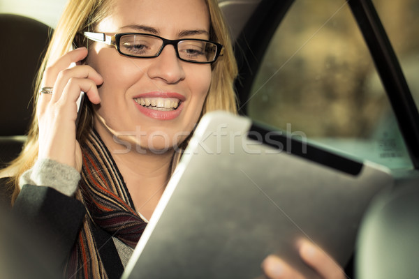 Young businesswoman driving in taxi, she using tablet computer a Stock photo © Kzenon