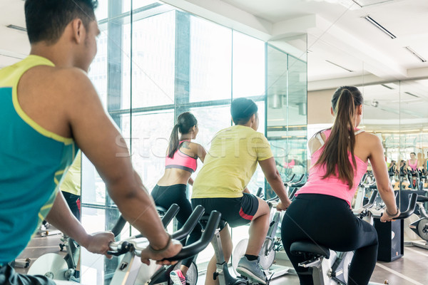 Fit women burning calories during indoor cycling class Stock photo © Kzenon