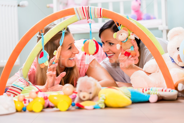 Stock photo: Women furnishing baby room preparing play bar for sucklings