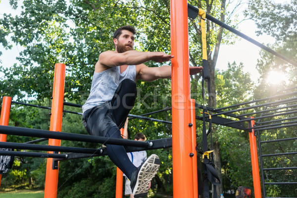 Determined handsome man doing extreme single-leg squats Stock photo © Kzenon