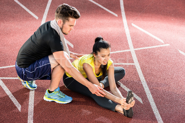 Man and woman on cinder track of sports arena stretching Stock photo © Kzenon