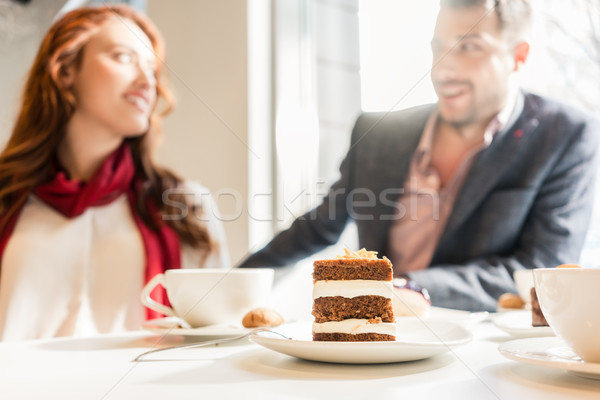 Delicious layered cake served with coffee on the table of a young couple Stock photo © Kzenon