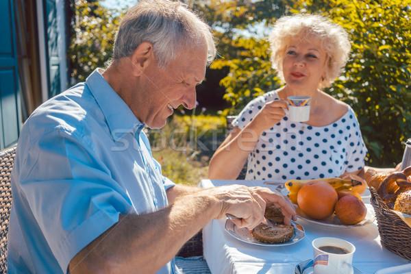 Senior woman and man having breakfast sitting in their garden Stock photo © Kzenon