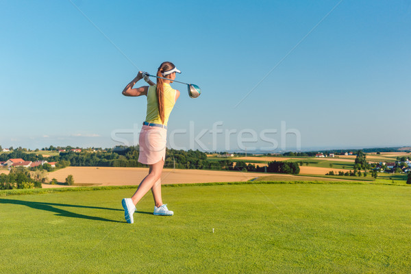 Professional female golf player smiling while swinging a driver club Stock photo © Kzenon