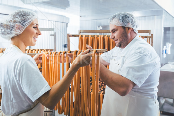 Woman working in butchery putting sausages on beam in rack Stock photo © Kzenon