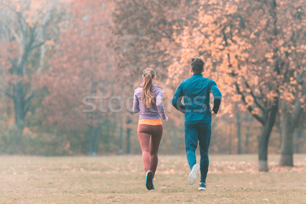 Fall running in a park, seen from behind couple Stock photo © Kzenon