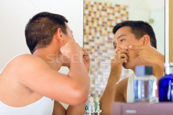 Asian uomo brufolo faccia specchio bagno Foto d'archivio © Kzenon