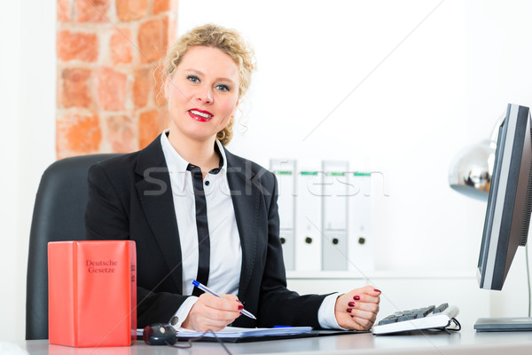 Stock photo: Lawyer in office with law book working on desk
