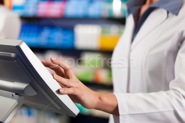 Female pharmacist at the cashier in pharmacy Stock photo © Kzenon