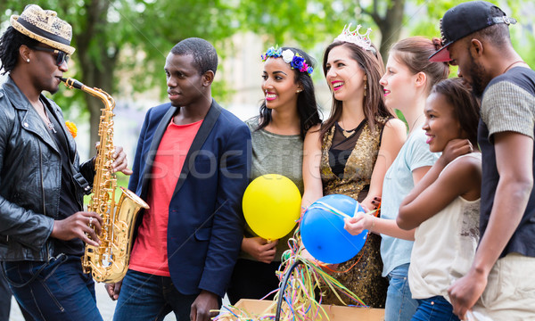 Stock photo: Street artist playing saxophone for multi-ethnic party group