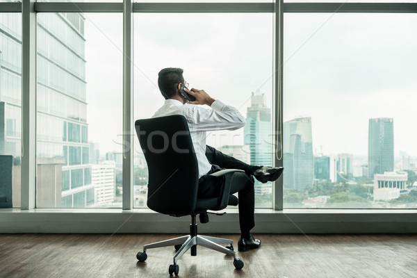 Rear view of businessman talking on phone while sitting down Stock photo © Kzenon
