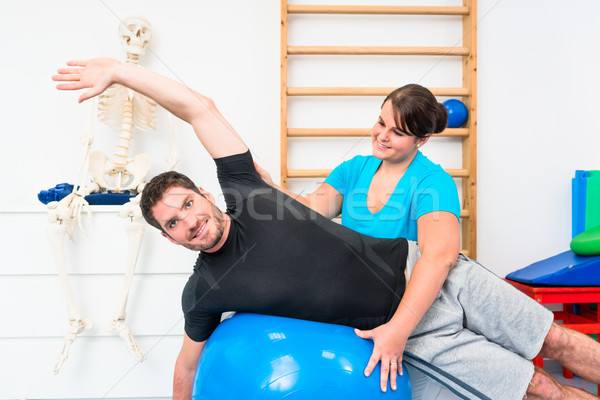 Young man exercising on swiss ball in physiotherapy Stock photo © Kzenon
