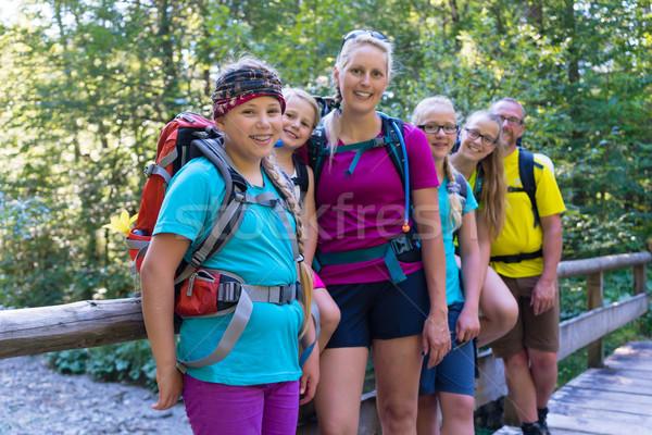 Family hiking in the forest standing on little bridge Stock photo © Kzenon