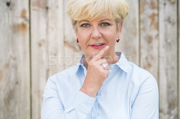 Portrait of an active senior woman looking at camera with a pens Stock photo © Kzenon