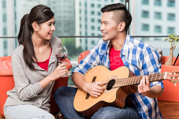 After moving together young man plays love song for his girlfrie Stock photo © Kzenon