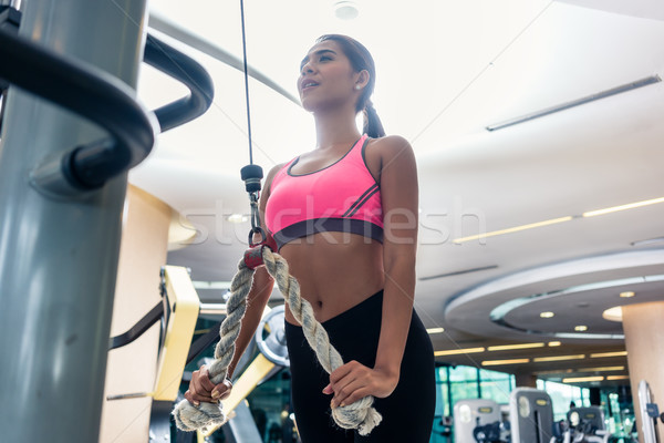 Stock photo: Low-angle view of a beautiful woman exercising cable rope tricep