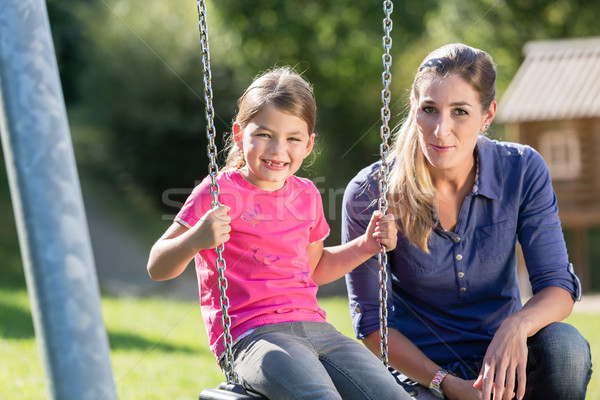Woman with laughing girl on swing having fun together Stock photo © Kzenon