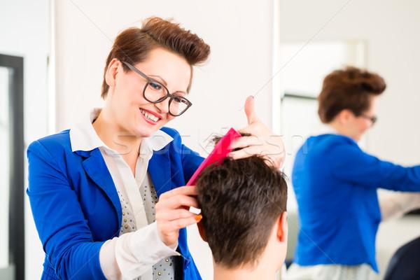 Hairdresser trimming man hair in barbershop Stock photo © Kzenon