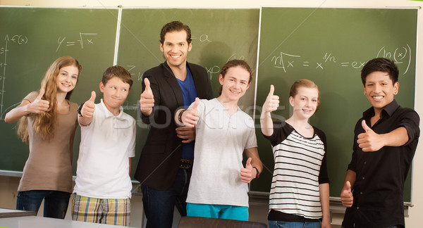 Teacher motivating students in school class Stock photo © Kzenon