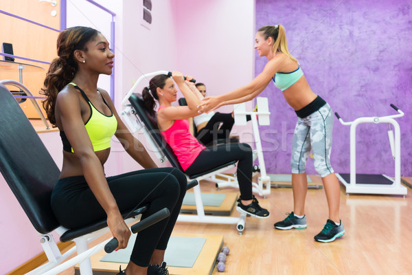 young woman exercising during group workout in a modern fitness  Stock photo © Kzenon