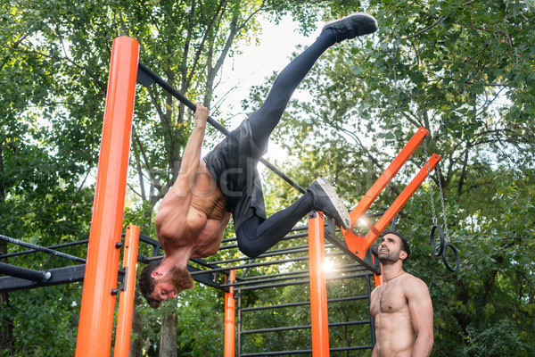 Shirtless bodybuilder hanging on horizontal bar during workout Stock photo © Kzenon