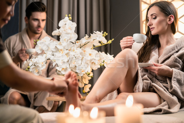 Stock photo: Beautiful woman drinking tea during therapeutic foot massage